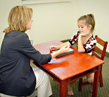 Dr. Kelderman interacts with a child during a pediatric neuropsychological evaluation.