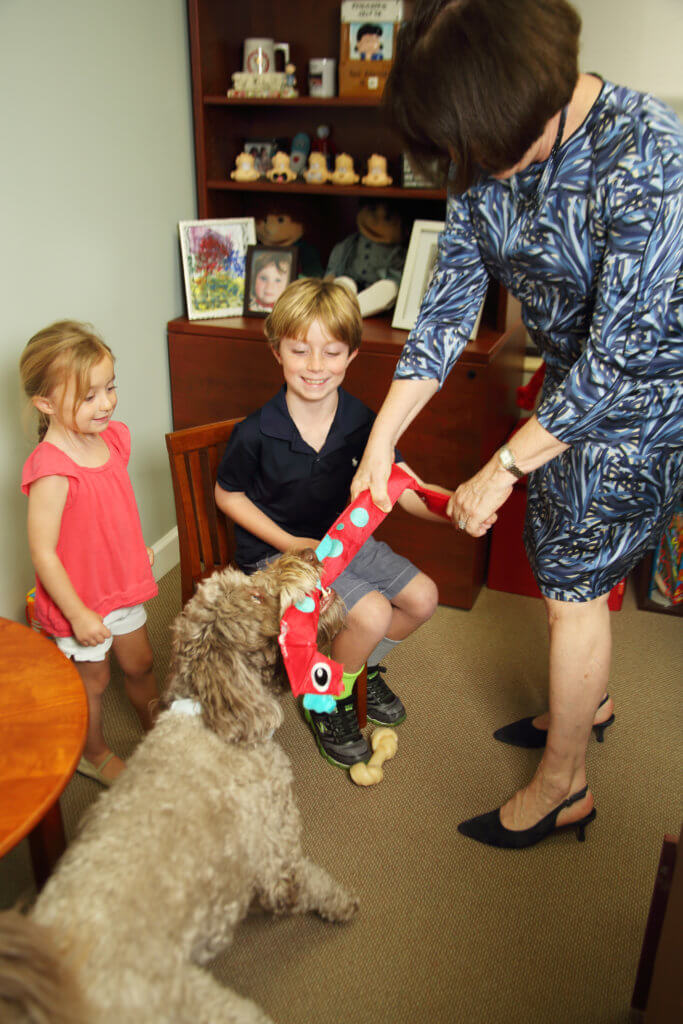 Dr. Kershner and some children play with Augie the office dog.