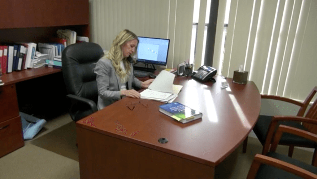 Dr. Kelderman reviews paperwork at her desk.