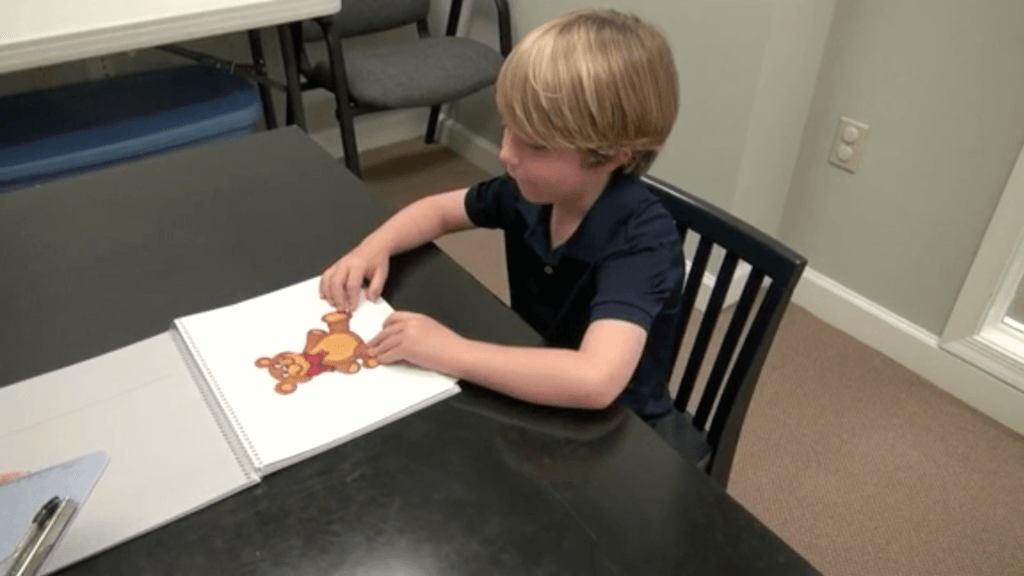A young patient flips to a page with a teddy bear in a spiral book.